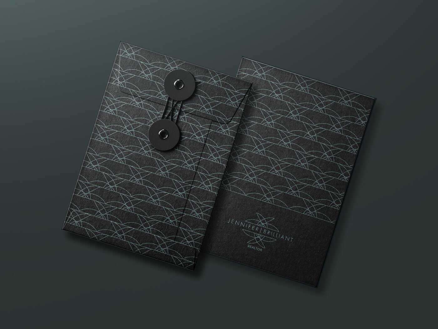 Jacober Creative envelope design for Realtor Jennifer Brilliant. Black folder with pattern and logo