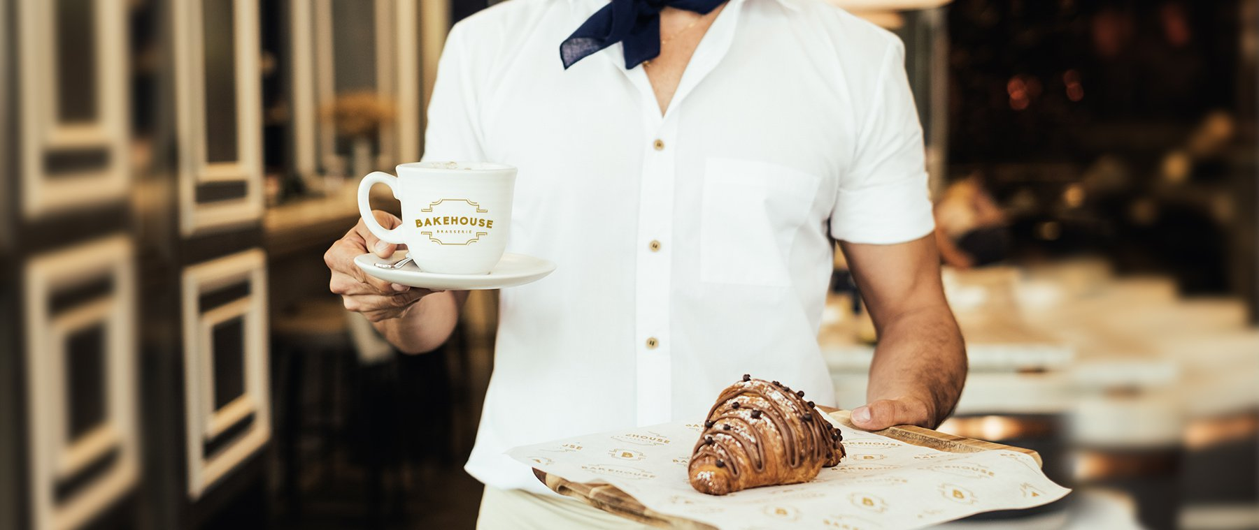 Jacober Creative identity design for Bakehouse Brasserie - Photo of a waitress holding a branded mug and pastry